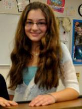 Elizabeth Nisly smiles behind her spelling bee trophy