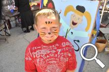 Adam Belcher shows off his painted face from Thursday's kid's art activities - these continue on Friday
