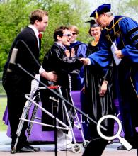 Marcus Meyers (center) receives his diploma and congratulations from Dr. James Harder, Bluffton University president, during Bluffton's commencement ceremony on May 6. Aiding Meyers is one of his 2011-12 personal care assistants on campus, fellow student Evan Skilliter.